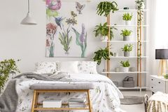 White bedroom interior with many fresh plants, king-size bed, material painting with floral pattern and bench with b. Real photo of white bedroom interior with stock image