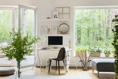 Real photo of white living room interior with big window, glass door, fresh plants, wooden desk with mockup computer and simple po