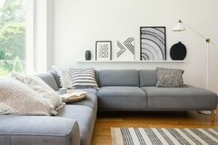 Real photo of white Scandi sitting room interior with metal lamp, corner sofa with cushions and modern art posters stock image