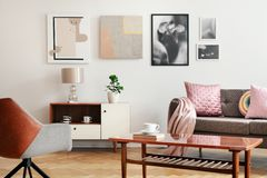 Real photo of white sitting room interior with poster on wall, couch with cushions and blanket, wooden coffee table with book and. Cup and plant on cupboard stock photo