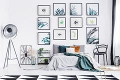 Real photo of a wide bed standing between a chair and a shelf, l. Amp and a clock in a spacious bedroom interior with triangle rug and wall full of paintings royalty free stock images