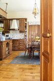 Real photo of a wooden kitchen interior with cupboards, dining t. Able, chairs and lamp. View through a door stock photo