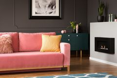Real photo of yellow pillow placed on powder pink settee standing in dark sitting room interior with fresh plants and eco. Fireplace stock images