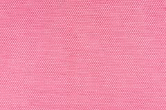 Real, pink knitted fabric fragment made of synthetic fibres textured background, with delicate pattern. Real, pink knitted fabric fragment made of synthetic royalty free stock photo
