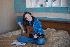 Real portrait of a young woman learning to play acoustic guitar. the concept of creativity stock image