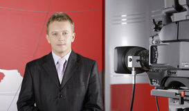 Real Presentor in TV studio in front of camera. TV studio with video camera and news presenter royalty free stock images