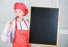 She is a real professional. Chief cook teaching master class. Pretty woman licking spoon at empty blackboard. Master stock photos