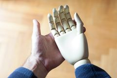 Real hand holding prosthetic hand. Real and prosthetic hand stock image