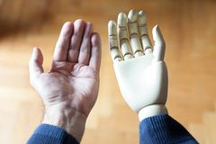 Real and prosthetic arm. Real and prosthetic hand stock photography