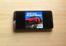 Real Racing 3 game app. On smartphone kept on wooden table royalty free stock images