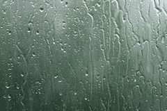 Real rain drops on window glass in high resolution. Backdrop Stock Image
