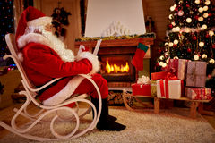 Real Santa Claus enjoying in warm Christmas atmosphere. Real Santa Claus enjoying on rocking chair in warm Christmas atmosphere in decorated loving room Stock Photo