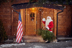 Real Santa Claus front his wooden house royalty free stock images