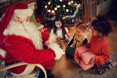 Real Santa Claus gives presents to kids stock images