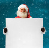 Real Santa Claus holding white blank sign for your text. / Merry Christmas & New Year's Eve concept / Closeup on blurred blue background Stock Image