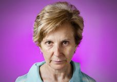 Real serious woman portrait over purple background stock photos
