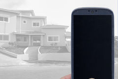 Real state application. Smatrphone and house. Idea for smartphone home security system, monitoring system, real state applications, contractor, architecture stock photo