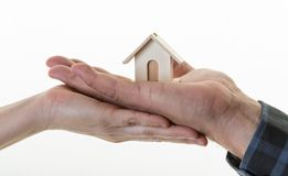 Real State Concept. Hands Holding a House. Hands of a couple holding a small house. Concept of sustaining a house between two people. Helping your partner in Royalty Free Stock Photography