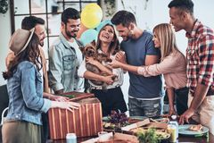 Real surprise. Happy young women holding a puppy and smiling while her friends standing around stock photos