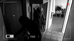 Real surveillance cameras caught and recorded the burglar breaking into the house,came across a dog and runs away.  stock footage