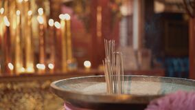 Real time shot of incense in a temple in Bangkok, Thailand. Candles are burning in the background.