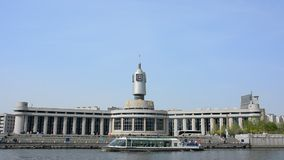 Real time video of Tianjin railway station with tourist boat is crossing the river. stock footage