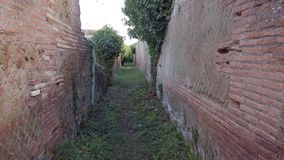 Real time walking in the past, through ancient road and roman empire ruins walls. In Ostia Antica ancient Rome village stock footage