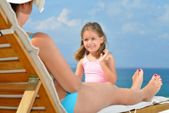 Real toddler girl relaxing with her mother on the sunbed Royalty Free Stock Images