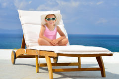 Real toddler girl relaxing on the sunbed Stock Image