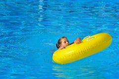 Real toddler girl relaxing at swimming pool Stock Photos