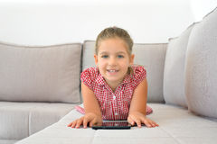 Real toddler girl working homework with tablet device Stock Photos