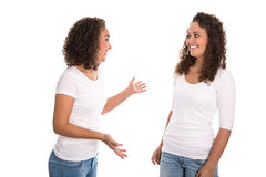 Real twins talking together: isolated over white background royalty free stock photography