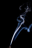 Real twisting smoke. Real smoke flowing up from a burning incense stick, isolated on black with tip of stick showing at extreme bottom of image Royalty Free Stock Photo
