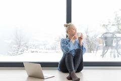 Woman drinking coffee and using laptop at home. Real Woman Using laptop on the floor Drinking Coffee Enjoying Relaxing at cold winter day Royalty Free Stock Photos