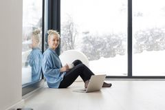 Woman drinking coffee and using laptop at home. Real Woman Using laptop on the floor Drinking Coffee Enjoying Relaxing at cold winter day Stock Images