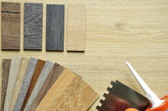 Real wood panel and laminated samples on a wooden background.Col. Samples of laminate and vinyl floor tile on wooden Background Royalty Free Stock Photography