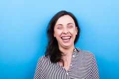 Real young woman laughing natural to the camera. On blue background in studio Royalty Free Stock Photos