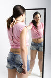 Real young woman looking in a mirror Stock Photography