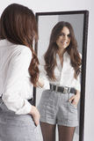 Real young woman looking in a mirror Royalty Free Stock Image