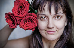Real young womenl with roses. The beautiful young  woman with a bouquet of red roses Stock Image