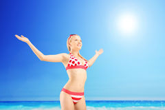 Realaxed female tourist spreading her arms and gesturing freedom. Next to sea on a sunny day Stock Photo