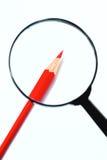 Reales Vergrößerungsglas und roter Bleistift Stockfoto