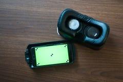 Realidade virtual, VR, capacete e smartphone com a tela verde para a tela chave do croma Fotos de Stock
