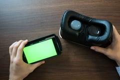 Realidade virtual, VR, capacete e smartphone com a tela verde para a tela chave do croma Imagem de Stock Royalty Free