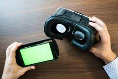 Realidade virtual, VR, capacete e smartphone com a tela verde para a tela chave do croma Fotos de Stock Royalty Free