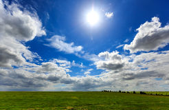 Realistic blue cloudy sky with bright sun over green meadow fiel Royalty Free Stock Images