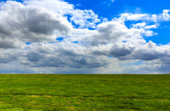 Realistic blue cloudy sky with bright sun over green meadow fiel Stock Images