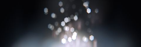 Realistic bokeh with geometric hexagonal iris. Dark abstract background with light particles out of focus. Long horizontal format Royalty Free Stock Photo