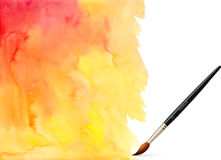 Realistic brush on orange watercolor background Stock Photos