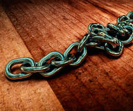 Realistic 3D model of a metal chain on the wooden floor. 3d rend Royalty Free Stock Photos
